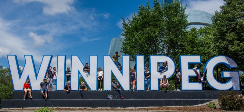 Students standing in front of giant letters spelling out Winnipeg
