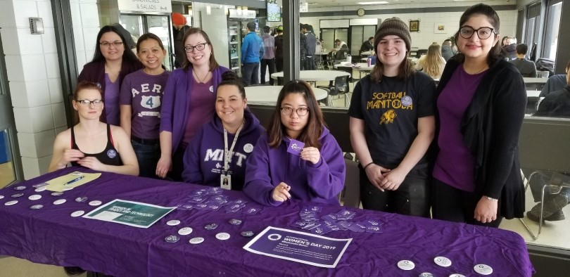 Women in Trades and Technology student group sitting at a table selling merchandise